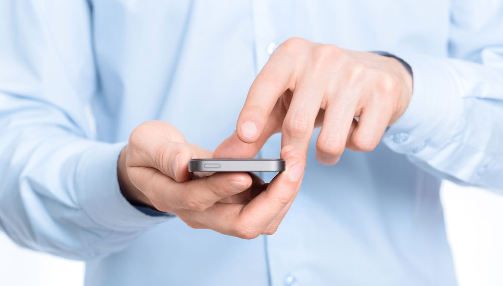Businessman holding and touching screen on a mobile phone