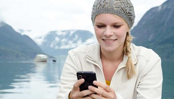 Girl checking her smartphone in front of lake and mountains