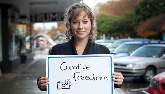 Portrait of Alana Barber holding the sign Creative Freedom