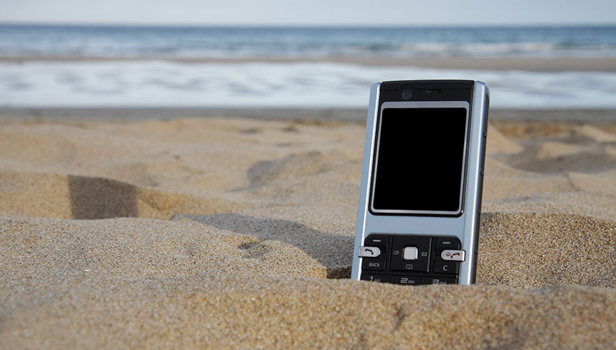 A mobile phone with blank black screen sits in the sand at the beach.