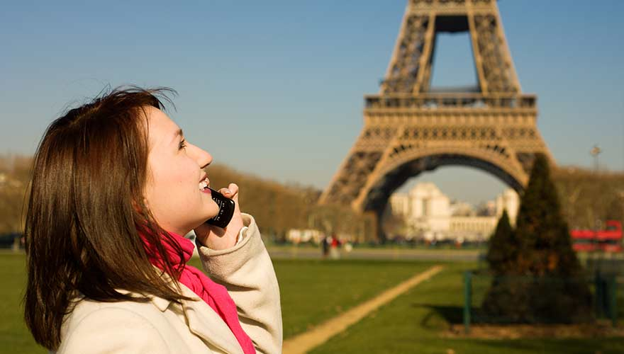 Woman talking on the phone in front of the Eiffel tower
