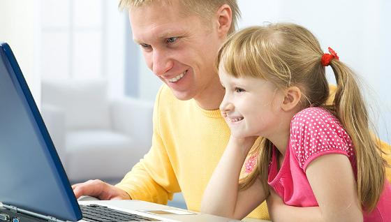 Little girl on laptop with adult