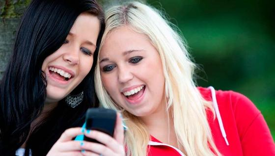 Two women looking at a mobile phone and laughing