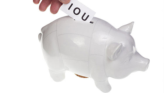 Hand placing an IOU note into a piggy bank