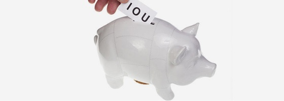 A hand places an IOU into a ceramic piggy bank.