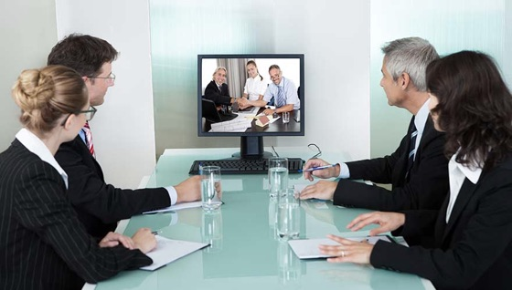 Hour business people gather around a screen for a remote meeting enhancd by HD Voice.